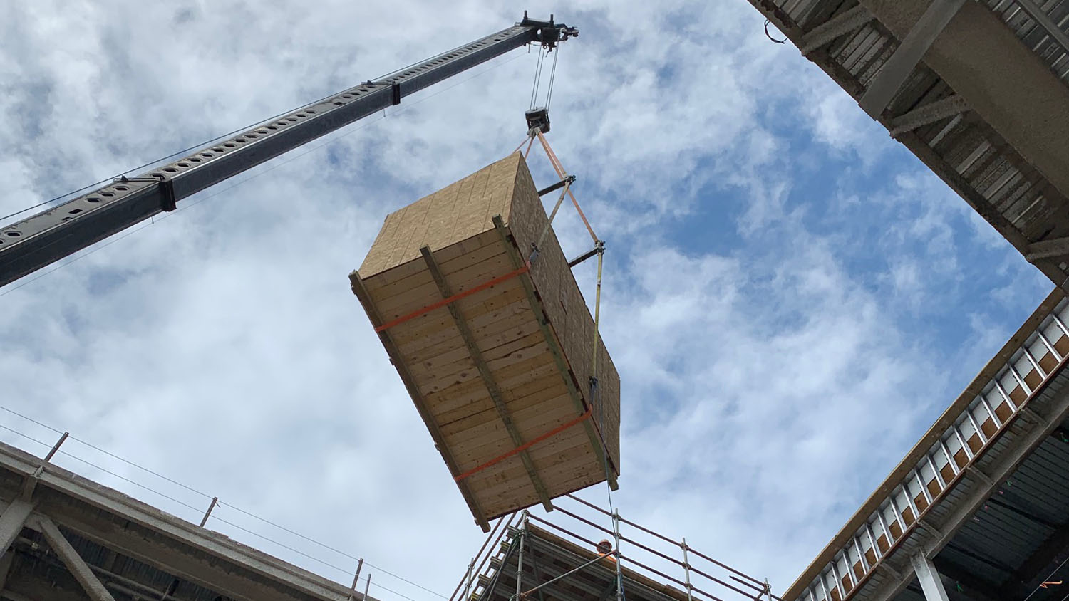 A wooden crate being hoisted by a crane into a building with a blue sky.